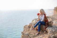Café bebendo da mulher bonita que senta-se na costa rochosa imagem de stock