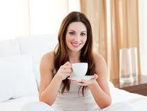 Café bebendo da mulher Charming que senta-se na cama fotos de stock