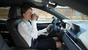 Café bebendo da mulher de negócios ao conduzir o carro vídeos de arquivo