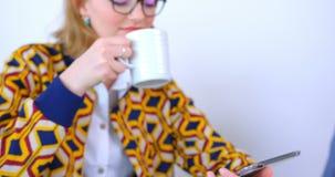 Café bebendo da mulher de negócios caucasiano bonita e utilização da tabuleta digital no escritório moderno 4k vídeos de arquivo