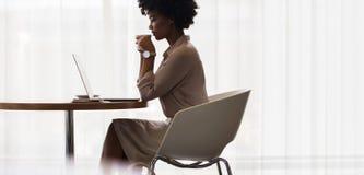 Café bebendo da mulher de negócios e vista do portátil Fotografia de Stock