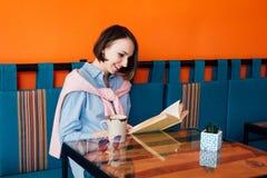 Café bebendo da mulher e leitura de um livro em um café Imagem de Stock Royalty Free