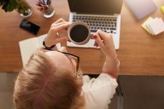 Café bebendo da mulher em sua mesa Imagem de Stock Royalty Free