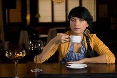Café bebendo da mulher em um contador da barra imagem de stock