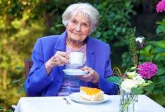 Café bebendo da mulher idosa na tabela do jardim imagem de stock royalty free
