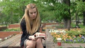 Café bebendo da mulher loura nova bonita e leitura de um livro no parque do verão filme