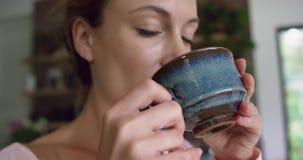 Café bebendo da mulher na cozinha na casa confortável 4k video estoque