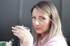 Café bebendo da mulher na manhã no foco macio do restaurante nos olhos imagens de stock