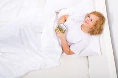 Café bebendo da mulher nova na cama foto de stock