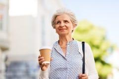 Café bebendo da mulher superior na cidade do verão fotografia de stock