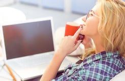 Café bebendo da senhora na frente do portátil Imagem de Stock Royalty Free