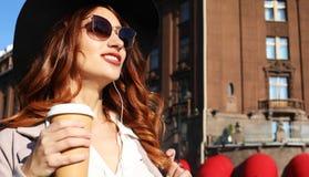 Café bebendo de sorriso da jovem mulher à moda ao andar em uma rua da cidade imagens de stock