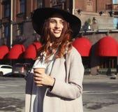 Café bebendo de sorriso da jovem mulher à moda ao andar em uma rua da cidade imagens de stock royalty free