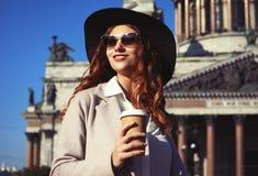 Café bebendo de sorriso da jovem mulher à moda ao andar em uma rua da cidade fotografia de stock
