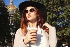 Café bebendo de sorriso da jovem mulher à moda ao andar em uma rua da cidade fotos de stock