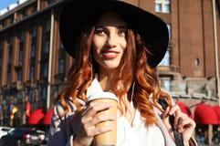 Café bebendo de sorriso da jovem mulher à moda ao andar em uma rua da cidade imagem de stock royalty free