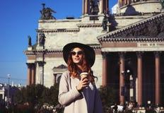Café bebendo de sorriso da jovem mulher à moda ao andar na A.A. imagens de stock royalty free