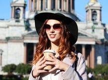 Café bebendo de sorriso da jovem mulher à moda ao andar na A.A. foto de stock