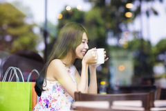 Café bebendo de sorriso da jovem mulher na loja do café Fotografia de Stock