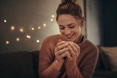 Café bebendo de sorriso da mulher no inverno em casa foto de stock royalty free
