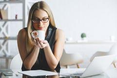 Café bebendo de sorriso da mulher no trabalho fotografia de stock royalty free