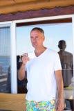 Café bebendo de sorriso do homem na costa de mar Fotografia de Stock Royalty Free