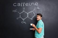 Café bebendo do cientista feliz sobre a estrutura química da molécula da cafeína imagens de stock
