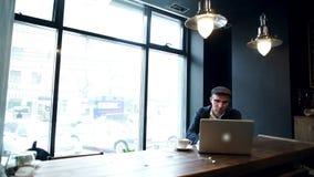 Café bebendo do homem novo na rua ao usar o tablet pc filme