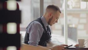 Café bebendo do homem novo no café e na tabuleta da utilização vídeos de arquivo