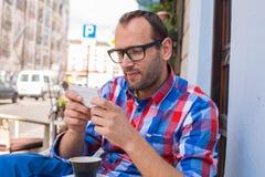 Café bebendo do homem novo no restaurante. Está guardarando um telemóvel. Foto de Stock