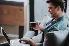 Café bebendo do homem seguro ao trabalhar em casa foto de stock