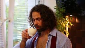 Café bebendo do homem sonolento, cansado na manhã na cozinha em casa filme