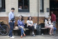 Café bebendo dos jovens que senta-se em um banco perto de um café Fotos de Stock