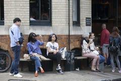 Café bebendo dos jovens que senta-se em um banco perto de um café Imagens de Stock Royalty Free