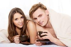 Café bebendo dos pares felizes na cama imagens de stock royalty free