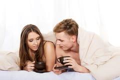 Café bebendo dos pares felizes na cama fotografia de stock