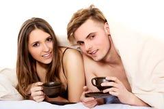 Café bebendo dos pares felizes na cama fotos de stock