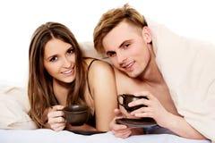 Café bebendo dos pares felizes na cama imagem de stock royalty free