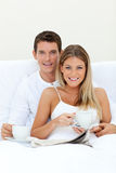 Café bebendo dos pares felizes que encontra-se em sua cama fotos de stock royalty free