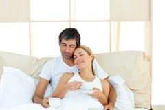 Café bebendo dos pares positivos que encontra-se na cama imagens de stock royalty free