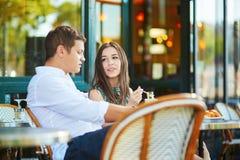 Café bebendo dos pares românticos novos em um café exterior acolhedor em Paris, França Imagem de Stock