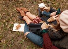 Café bebendo dos pares românticos que relaxa no parque no outono fotos de stock
