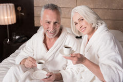 Café bebendo envelhecido agradável feliz dos pares na cama Imagem de Stock