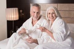 Café bebendo envelhecido de sorriso dos pares na cama Imagem de Stock