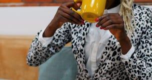 Café bebendo executivo fêmea ao trabalhar na tabuleta digital filme