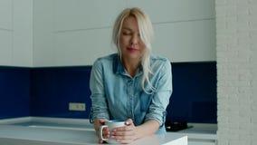 Café bebendo novo da mulher branca na cozinha moderna vídeos de arquivo