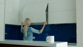 Café bebendo novo da mulher branca na cozinha moderna filme