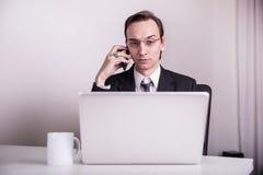Café bebendo novo do homem de negócio e fala em um telefone celular no escritório Imagem de Stock Royalty Free
