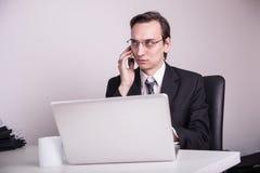 Café bebendo novo do homem de negócio e fala em um telefone celular no escritório Fotos de Stock Royalty Free