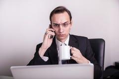 Café bebendo novo do homem de negócio e fala em um telefone celular no escritório Imagens de Stock